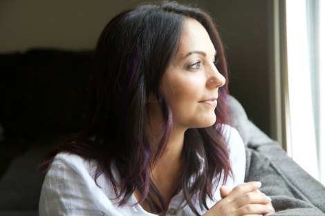 Woman gazes out living room window