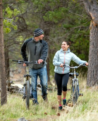 Young couple talking while they push their bikes through a trail